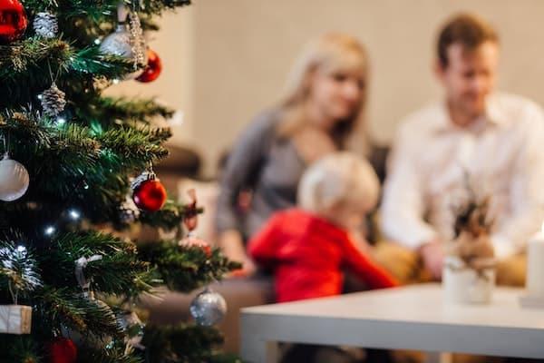 Familie neben Weihnachtsbaum
