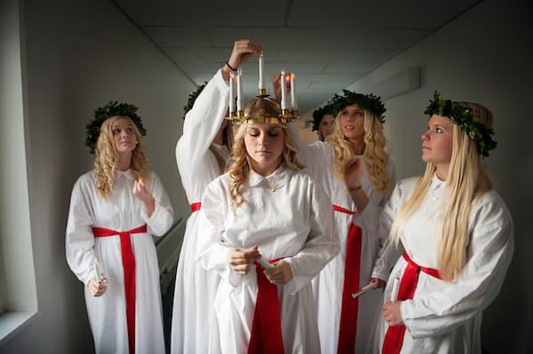 Lucia mit weißem Gewand, rotem Band und Kranz mit Kerzen